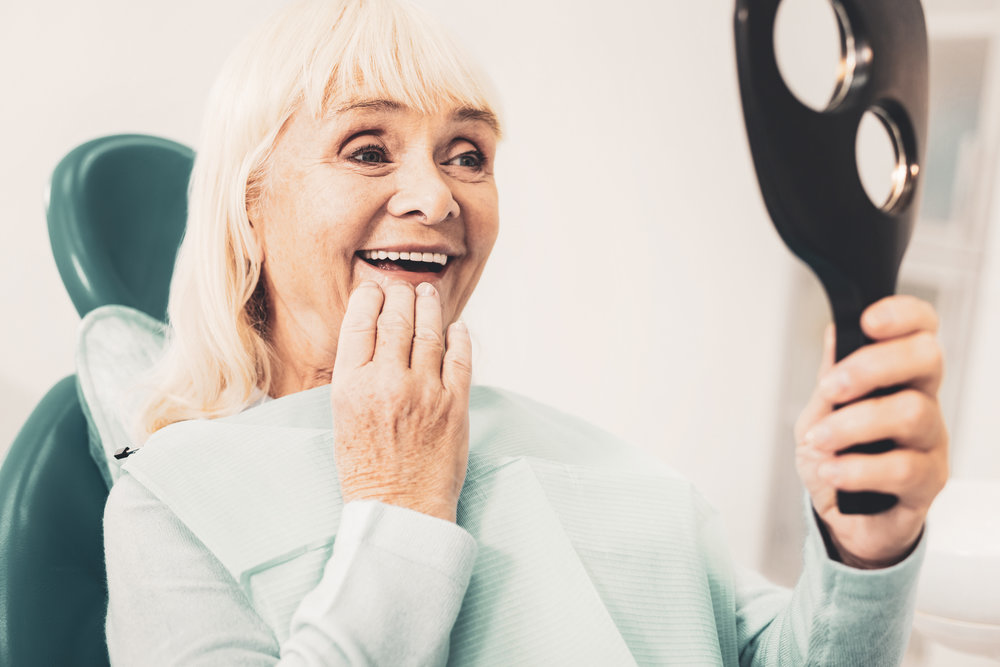White smile. Close up of mature smiling woman holding mirror and viewing her new denture while touching her chin with hand